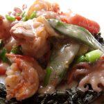 Fekete rizottón tálalt tenger gyümölcsei