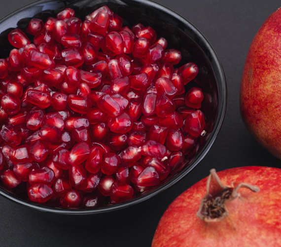 Pomegranate seeds in a black bowl
